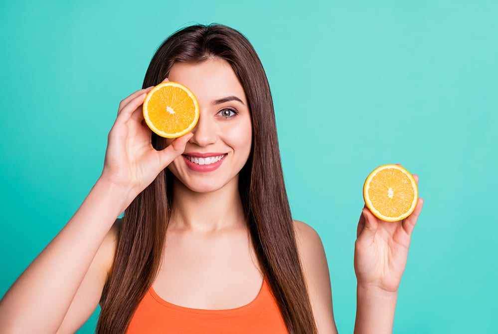 Woman Holding Oranges - Vitamin C - The Grandfather of Traditional Antioxidants
